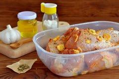 未加工的小鸡腿用香料,橄榄油,大蒜,盐为油煎做准备 烹调的肉成份 免版税库存图片