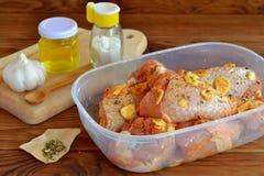 未加工的小鸡腿用香料,橄榄油,大蒜,盐为油煎做准备 烹调的肉成份 免版税库存照片