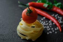 未加工的意大利细面条面团用新鲜的蕃茄、粗糙的香菜海盐绿色叶子和辣椒 库存照片