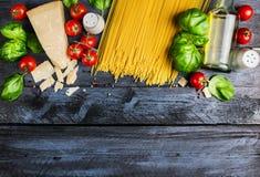 未加工的意粉用蕃茄,蓬蒿、巴马干酪和油,烹调在蓝色土气木背景的成份,顶视图 免版税库存图片
