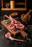 未加工的放在架子上的羊羔用在切板的香料 免版税图库摄影