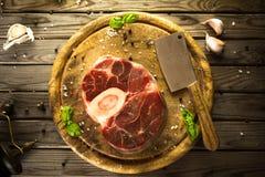 未加工的新十字架切了小牛肉用大蒜、胡椒和调味料在木切板有屠户砍肉刀的 免版税图库摄影