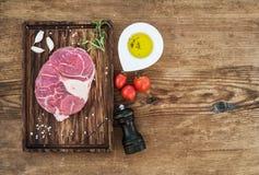 未加工的新牛肉肉十字架为ossobuco切开了用拨蒜、西红柿、迷迭香、胡椒、油和盐  免版税库存图片