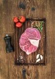 未加工的新牛肉肉十字架为ossobuco切开了用拨蒜、西红柿、迷迭香、胡椒和盐在服务 图库摄影