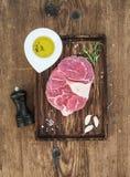 未加工的新牛肉肉十字架为ossobuco切开了用拨蒜、迷迭香、胡椒、油和盐在服务板 库存照片