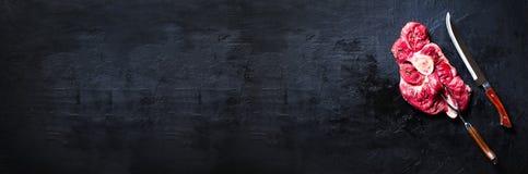 未加工的新鲜的肉牛排用西红柿、辣椒、大蒜、油和草本在黑暗的石头,具体背景 钞票 库存照片