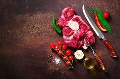 未加工的新鲜的肉牛排用西红柿、辣椒、大蒜、油和草本在黑暗的石头,具体背景 钞票 库存图片
