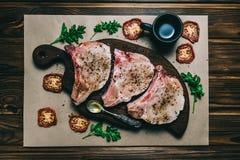 未加工的新鲜的肉猪肉牛排和调味料在一个黑暗的木背景板蜂蜜蕃茄板 免版税库存图片