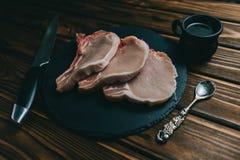 未加工的新鲜的肉猪肉牛排和调味料在黑暗的背景 图库摄影
