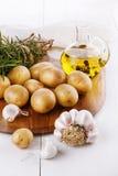未加工的有机土豆用迷迭香和大蒜在白色backgroun 库存照片