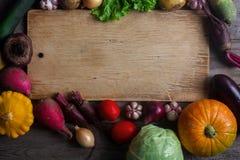 未加工的有机新鲜蔬菜和木板在土气样式 收割期,五颜六色的菜,健康生活方式 免版税库存图片