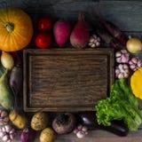 未加工的有机新鲜蔬菜和木板在土气样式 收割期,五颜六色的菜,健康生活方式 免版税图库摄影