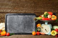 未加工的有机新鲜蔬菜的构成, texton的,在木棕色桌上的平衡粉笔板 免版税库存照片