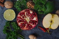 未加工的有机果子、绿色、菜和坚果在黑暗的石桌上 库存照片