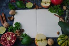 未加工的有机果子、绿色、菜和坚果在黑暗的石桌上 免版税库存图片