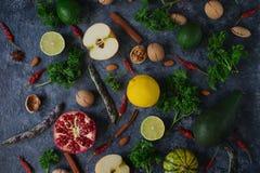 未加工的有机果子、绿色、菜和坚果在黑暗的石桌上 免版税库存照片