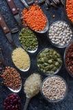 未加工的有机谷粒、种子和豆在木匙子和碗 免版税库存照片
