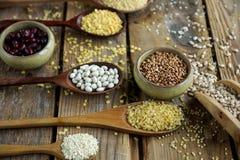 未加工的有机谷粒、种子和豆在木匙子在土气木背景 图库摄影