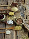 未加工的有机谷粒、种子和豆在木匙子在土气木背景 库存照片