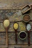 未加工的有机谷粒、种子和豆在木匙子在土气木背景 免版税库存照片