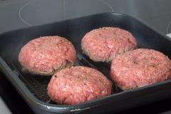 未加工的汉堡,在一个煎锅的牛肉在烹调表面在厨房里 库存图片