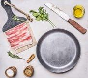 未加工的烟肉开胃片断在一个煎锅的有油,被刺中,草本、盐和香料木土气背景顶视图clos的 免版税库存照片