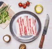 未加工的烟肉开胃片断在一个煎锅的有油,被刺中,草本、盐和香料木土气背景顶视图clos的 库存照片