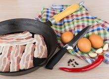 未加工的烟肉片断在煎锅的,鸡蛋,大蒜,胡椒 免版税库存照片