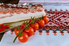 未加工的烟肉用香料和蕃茄在木桌上 图库摄影