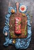 未加工的烤牛肉用草本和香料栓与在使用的木切板的一条绳索在黑暗的葡萄酒金属背景 免版税库存照片