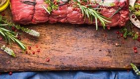 未加工的烤牛肉用草本和香料栓与在木背景,顶视图的一条绳索 免版税库存图片