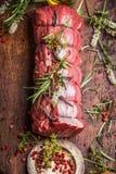 未加工的烤牛肉用草本和香料栓与在木背景,顶视图的一条绳索 库存照片