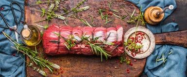 未加工的烤牛肉用草本栓与与烹调成份、油和香料的一条绳索在土气背景,顶视图 库存图片