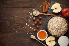 未加工的燕麦在有各种各样的成份的碗剥落在黑暗的土气木背景的早餐 库存照片