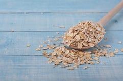 未加工的燕麦在木匙子剥落 免版税库存图片