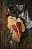 未加工的牛排丁骨牛排用牛至和迷迭香、盐、胡椒和ket 免版税库存图片