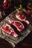 未加工的牛排用辣椒和大蒜 免版税库存照片
