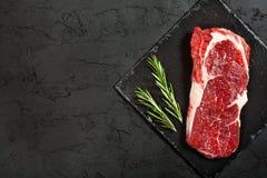 未加工的牛排用迷迭香和胡椒在一块黑暗的石头 免版税图库摄影