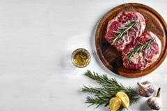 未加工的牛排用香料和成份烹调的在木切板和白色背景 库存图片