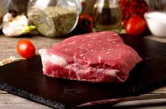 未加工的牛排黑色安格斯肉板材 免版税库存图片