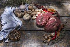 未加工的牛排,为烤,盐,胡椒,蕃茄,在木背景的大蒜准备 库存照片