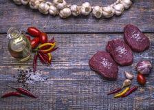 未加工的牛排,为烤,盐,胡椒,蕃茄,大蒜,额外在木背景的处女橄榄油准备 顶层 免版税库存图片