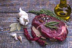 未加工的牛排,为烤,盐,胡椒,蕃茄,大蒜,额外在木背景的处女橄榄油准备 顶层 免版税库存照片