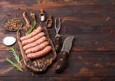 未加工的牛肉和猪肉香肠在老砧板有葡萄酒刀子的和叉子在黑暗的木背景 盐和胡椒与 免版税库存图片
