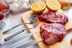 未加工的牛肉用桔子和别的在与咕咕声的木斩肉板 免版税图库摄影