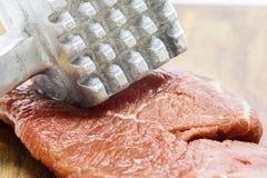 未加工的牛肉肉和锤子 免版税库存照片
