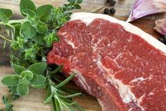 未加工的牛腰肉排用草本 免版税图库摄影