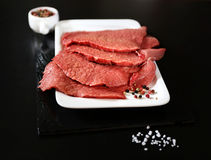 未加工的牛里脊肉、盐、胡椒和刀子 库存照片