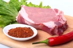 未加工的猪排用草本和香料在切板 为烹调准备 免版税库存图片