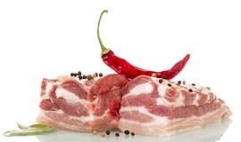 未加工的猪肉、在白色隔绝的红辣椒和香料 免版税图库摄影